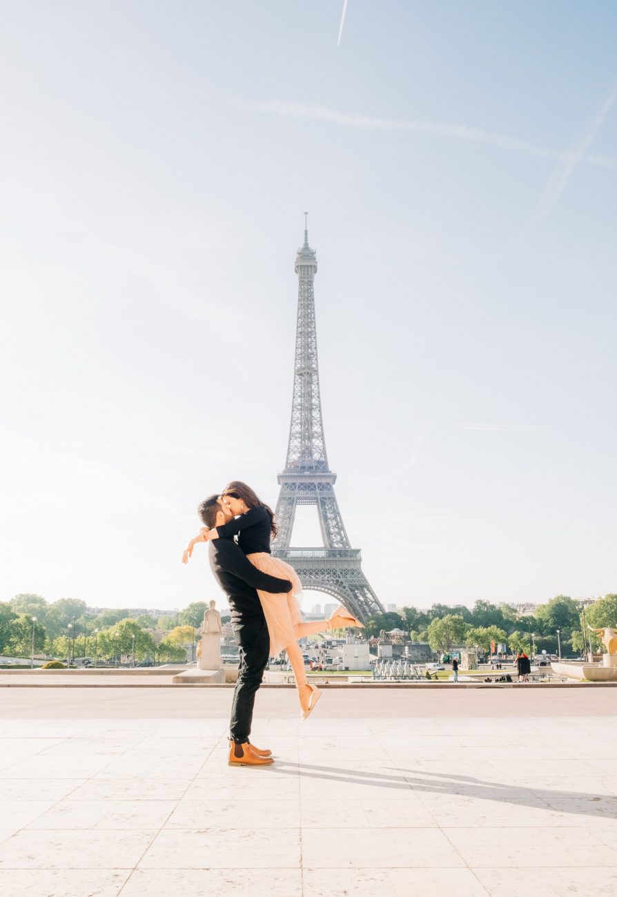 couple embraces near eiffel tower