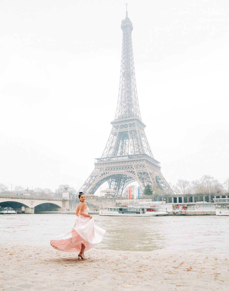 dancing in pink dress near river and eiffel tower