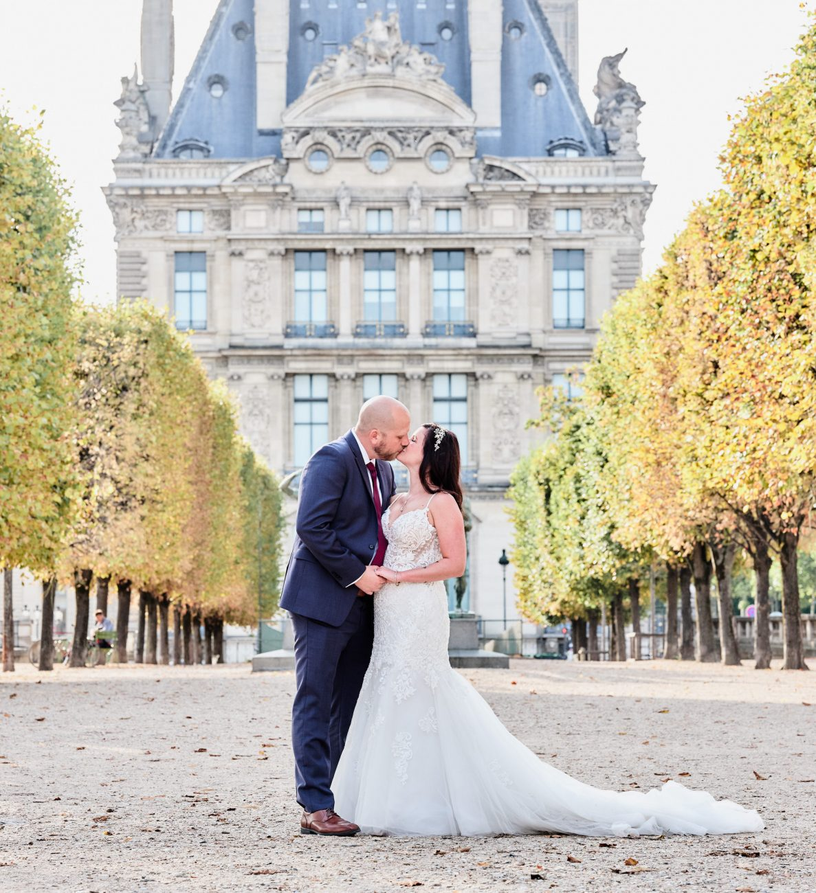 newlyweds kiss at the tuileries gardens in front of the louvre museum in paris